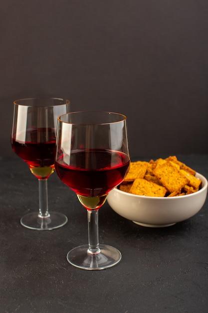 Una vista frontale bicchieri di vino con patatine all'interno del piatto su oscurità Foto Gratuite