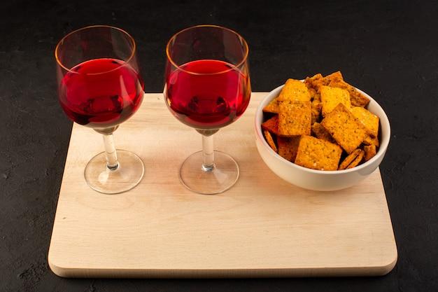 Una vista frontale bicchieri di vino con patatine all'interno del piatto sullo scrittorio di legno e scuro Foto Gratuite