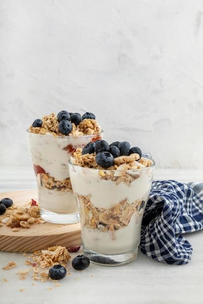 Vista frontale di bicchieri con cereali per la colazione e yogurt Foto Gratuite