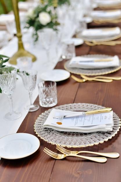 Vista frontale di bicchieri e posate servita sul tavolo di legno e targhetta stampata per gli ospiti Foto Gratuite