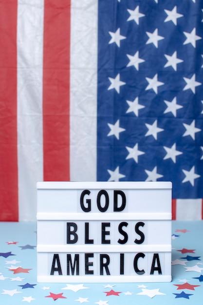 Вид спереди бог благословит америку знак с флагами Бесплатные Фотографии
