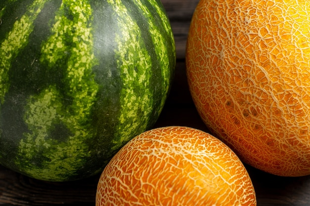 正面緑のスイカ丸い形が茶色の机の上のメロンと新鮮でジューシーなフルーツを形成 無料写真