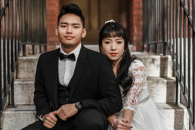 Vista frontale dello sposo e della sposa in posa insieme sui gradini Foto Gratuite
