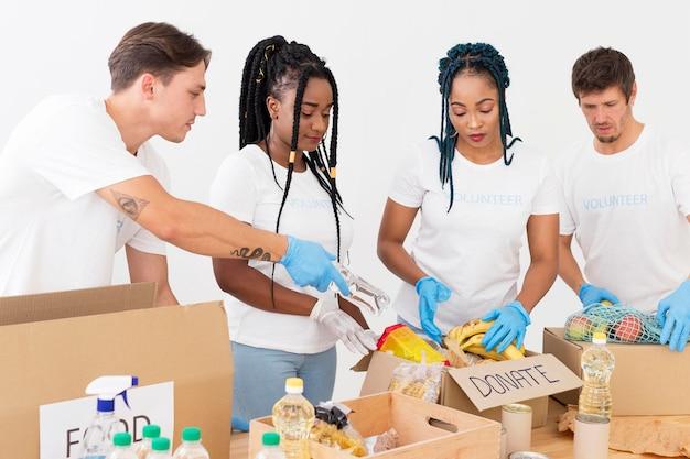 Vista frontale del gruppo di volontari che si prendono cura delle donazioni Foto Gratuite