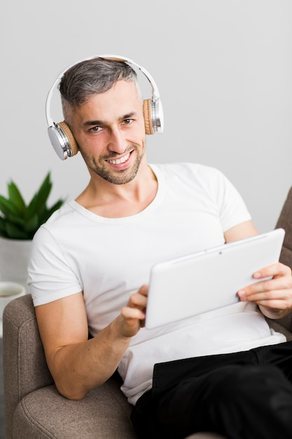 Front view guy with headphones smiles Free Photo