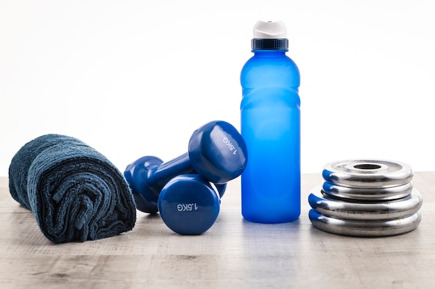Front view gym equipment with water and towel beside Free Photo