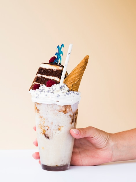 Front view of a hand holding a delicious milkshake Free Photo