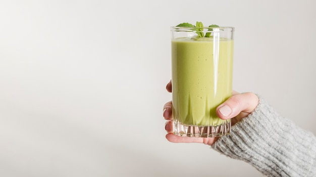 Front view hand holding green smoothie and mint in glass with copy-space Free Photo