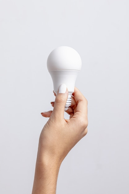 Front view of hand holding light bulb with copy space Free Photo