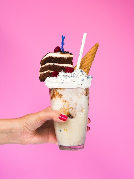 Front view of a hand holding a milkshake with pink background Free Photo