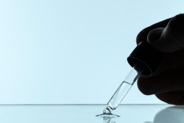 Vista frontale della mano che tiene la pipetta con liquido e copia spazio Foto Gratuite