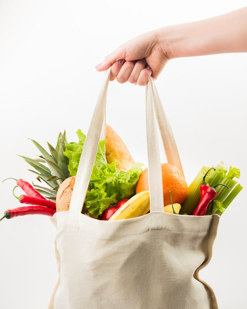 Front view of hand holding reusable bag with fruit and vegetables Free Photo