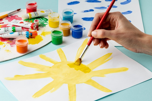 Front view of hand painting a sun Free Photo