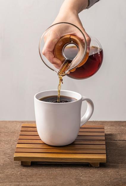 Vista frontale della mano che versa il caffè nella tazza Foto Gratuite