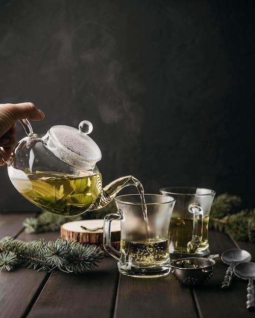 Вид спереди рука наливает чай в стакан Бесплатные Фотографии