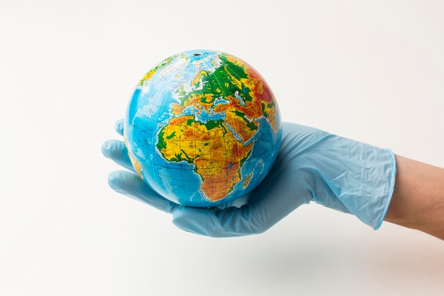 Front view of hand with gloves holding earth globe Free Photo