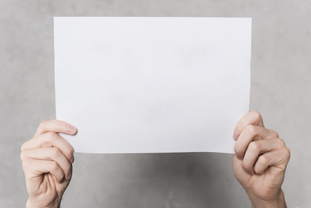 Front view of hands holding blank paper Premium Photo