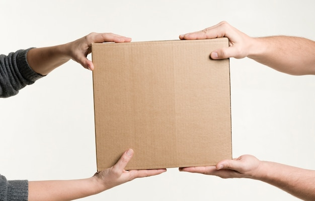 Front view of hands holding cardboard Free Photo