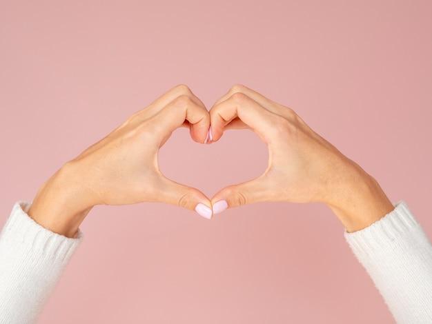 心臓ジェスチャーを示す正面図手 Premium写真