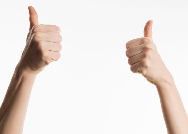 Vista frontale delle mani che mostrano i pollici in su Foto Gratuite