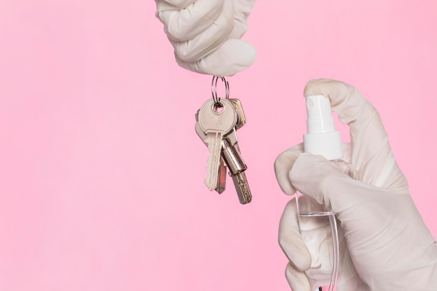 Front view of hands with surgical gloves disinfecting keys Premium Photo