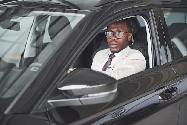 Vista frontale dell'uomo bello africano elegante serio di affari guida una macchina. Foto Gratuite