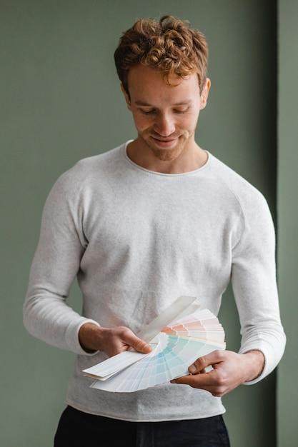 Vista frontale dell'uomo bello che intende ridipingere la casa usando la tavolozza della vernice Foto Gratuite