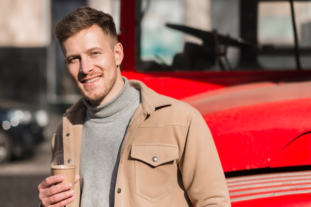 Front view of handsome man posing while holding coffee cup Free Photo
