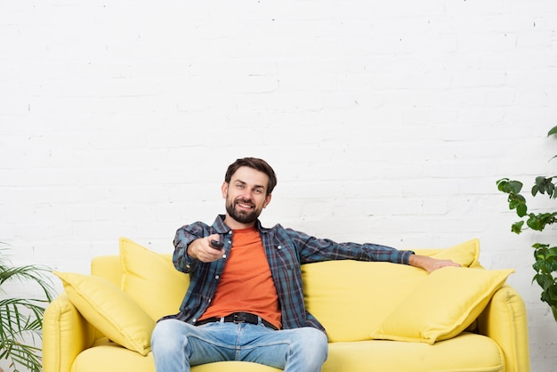 Front view handsome man watching tv Free Photo