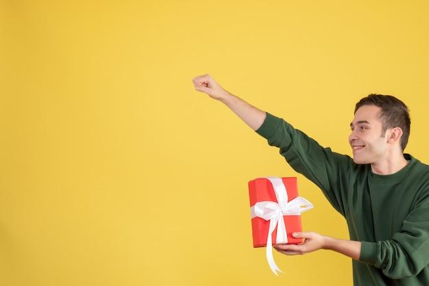 Вид спереди красивый молодой человек, держащий подарок, жест супергероя на желтом Бесплатные Фотографии
