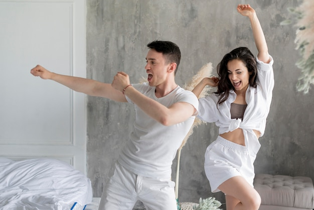 Front view of happy couple dancing at home Free Photo