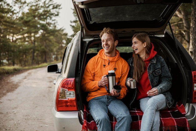 Front view of happy couple enjoying hot beverage in the trunk of the car Free Photo