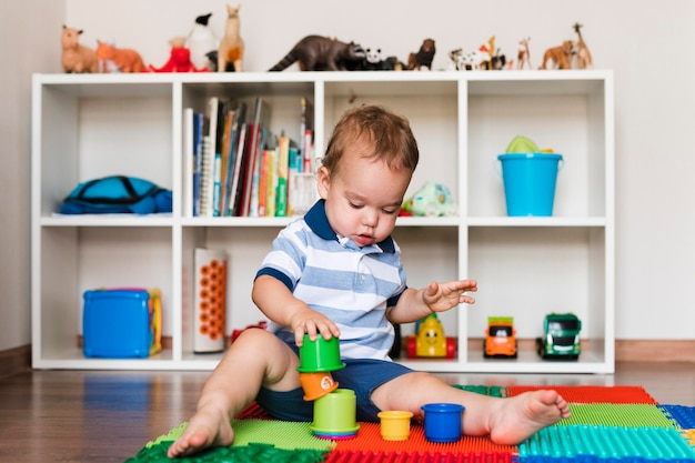 Front view of happy cute baby boy playing with toys Free Photo