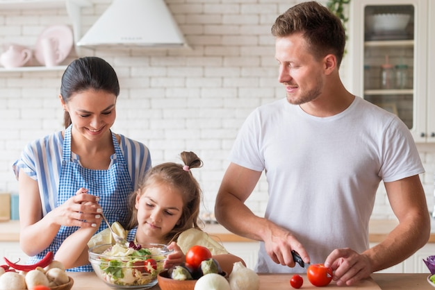 Front view happy family cooking together Free Photo