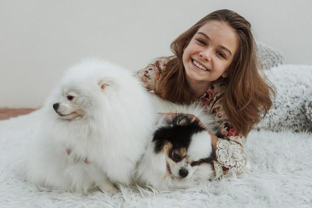 Вид спереди счастливая девушка и две пушистые собаки Бесплатные Фотографии