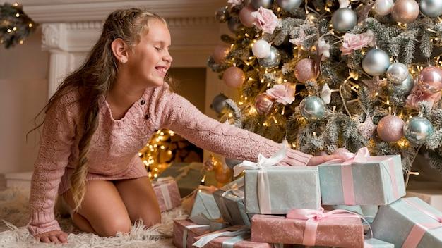 Vista frontale della ragazza felice con regali e albero di natale Foto Gratuite