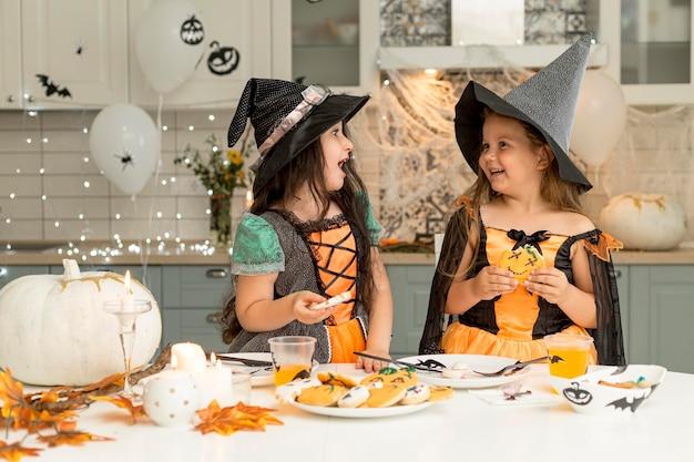 Vista frontale di ragazze felici in costume da strega Foto Gratuite