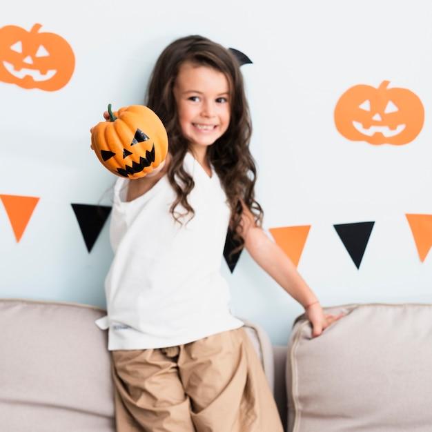 Вид спереди счастливая маленькая девочка держит тыкву Бесплатные Фотографии