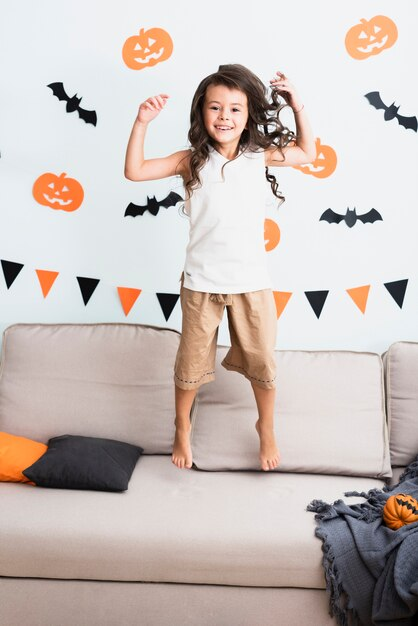 Front view happy little girl jumping on couch Free Photo