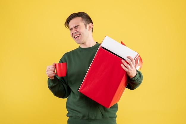 Вид спереди счастливый человек с зеленым свитером, держащий большой подарок и красную чашку, стоящий на желтом Бесплатные Фотографии