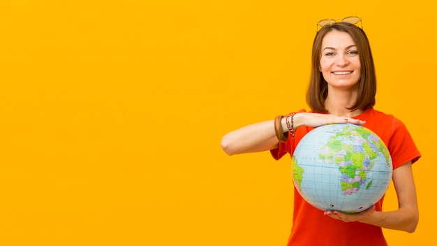 Front view of happy woman holding globe with copy space Free Photo