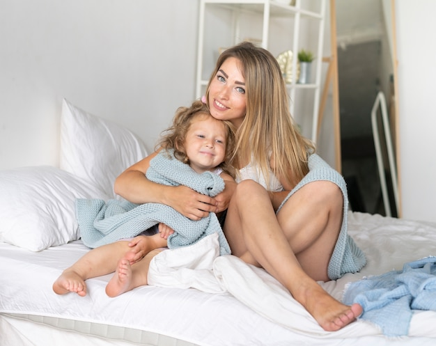 ベッドで娘と一緒に座っている正面幸せな女 無料写真