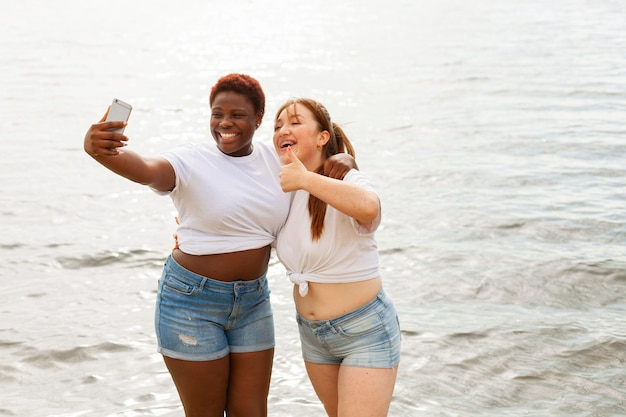 Front view of happy women taking selfie at the beach Free Photo