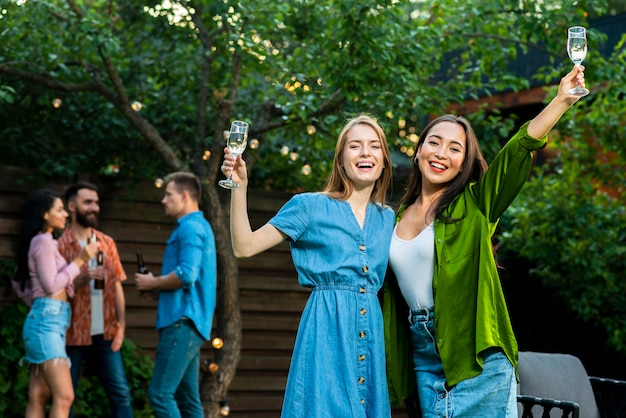 Front view happy young girls raising glasses Free Photo