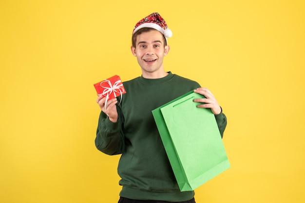Вид спереди счастливый молодой человек в шляпе санта-клауса, держащий зеленую хозяйственную сумку и подарок, стоящий на желтом Бесплатные Фотографии