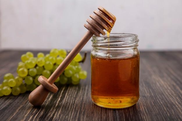 Miele di vista frontale in un barattolo con un cucchiaio di legno e uva verde e su un fondo di legno Foto Gratuite