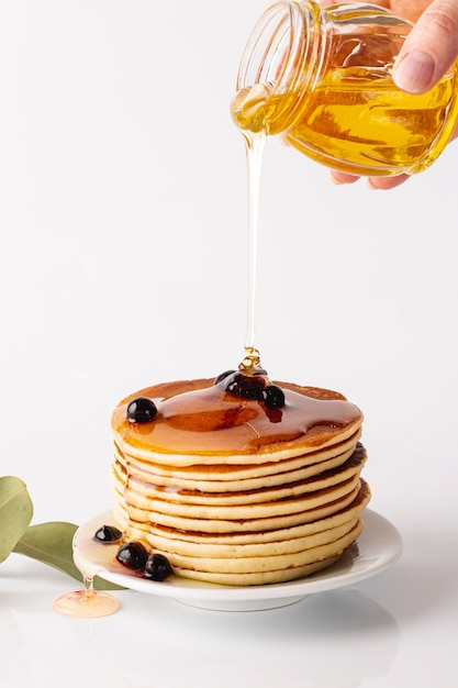 Front view honey poured over pancake tower on plate with blueberries Free Photo