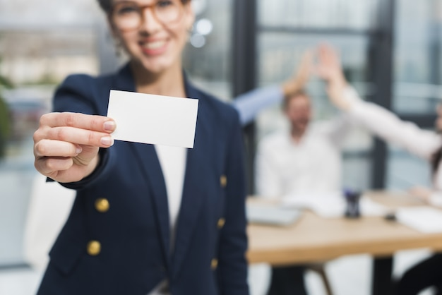Front view of human resources woman holding up business card Premium Photo