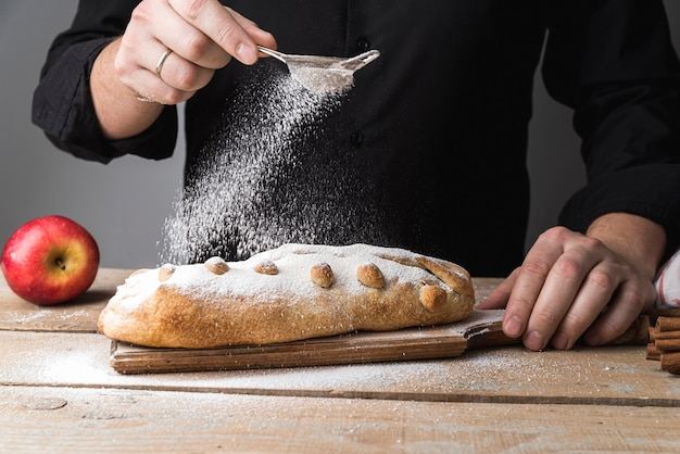 Front view individual pouring sugar on pastry Free Photo