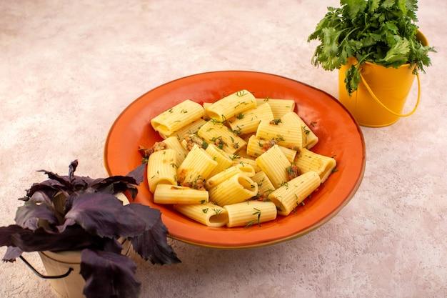 Una pasta italiana di vista frontale cucinata gustosa con verdure essiccate e salata all'interno di un piatto rotondo arancione con fiore sulla scrivania rosa Foto Gratuite